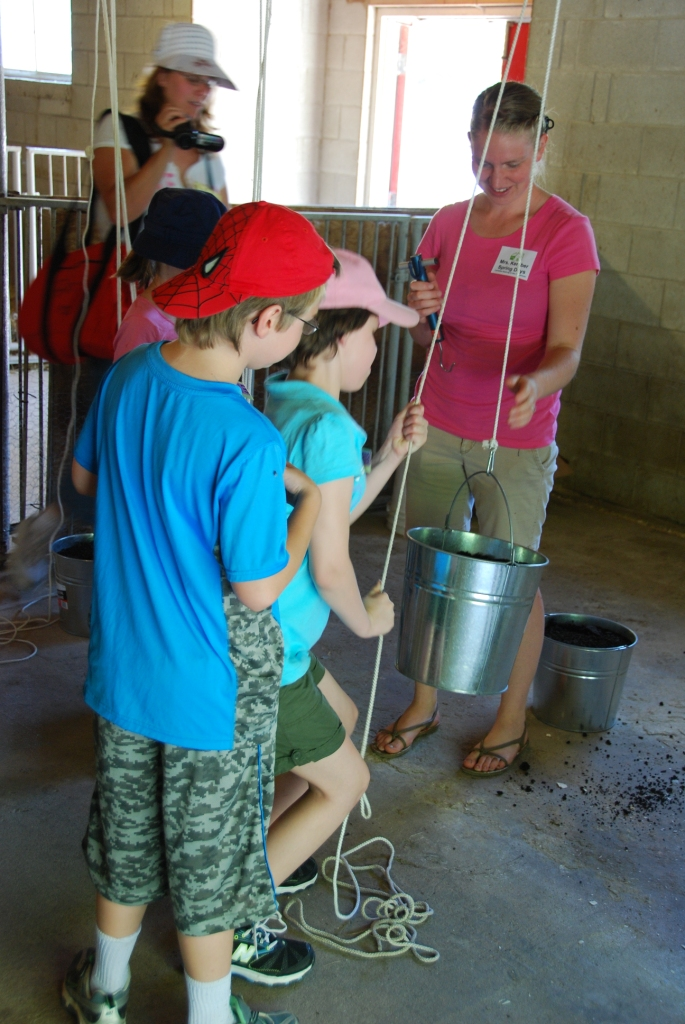 Person showing kids the use of a pulley using a rope and bucket